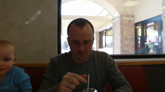 A father eating a milk shake with his toddler Stock Footage