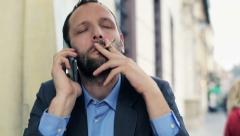 young businessman talking on cellphone and smoking cigarette in cafe - stock footage