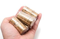 male asian hand holding a bunch of one dollar coins - stock photo