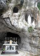 statue of the virgin mary in the grotto of lourdes attracts many pilgrims 3 - stock photo