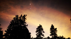 Stock Video Footage of Astrophotography Time Lapse of Stars and Red Clouds over Alpine Forest -Zoom In-