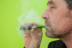 Man puffing on an e-cigarette Stock Photos