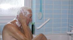 Senior man washing hair Stock Footage