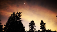 Stock Video Footage of 4K Astro Time Lapse of Stars & Red Clouds over Alpine Forest -Tilt Up-