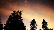 Stock Video Footage of 4K Astro Time Lapse of Stars & Red Clouds over Alpine Forest -Pan Right-