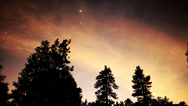 Stock Video Footage of 4K Astro Time Lapse of Stars & Red Clouds over Alpine Forest -Zoom In-
