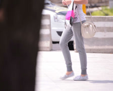 grey trousers long legs young adult woman walking street - stock footage