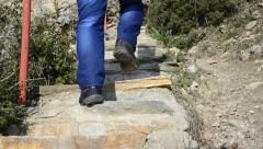 Hiker walks up ancient stone stairs Stock Footage