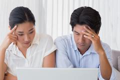 Worried couple using laptop together Stock Photos