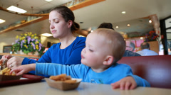 Little boy eating chicken strips with mom Stock Footage