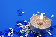 small candle with stars and copy space - stock photo