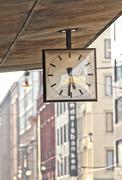 Street clock. Hanging clock on city walk. - stock photo