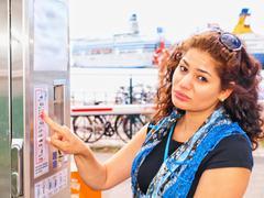 Unhappy brune, female, at ticket vending machine - stock photo