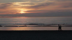 Two people walking on Beach during Sunset - stock footage