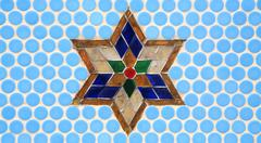 Colorful glass star decoration on blue wall Stock Photos