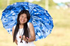 beautiful young thai girl under a blue sunshade - stock photo