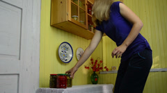 Girl prioritizes jars the cupboard with canned vegetables Stock Footage