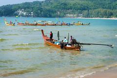 Phuket, thailand - 19 mar 2013: man cast off on wooden long boat in phuket, t Stock Illustration
