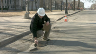 Stock Video Footage of Workman inspects potholes in the Street 4K