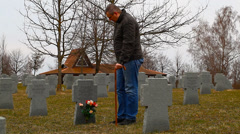 Man with walking stick near soldier's grave Stock Footage