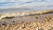 Stock Video Footage of River bank with pebbles and waves of splashing water.