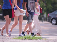 two beautiful young adult women and man walking on street - stock footage