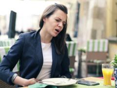 Businesswoman gets stomach ache during lunch in cafe NTSC Stock Footage