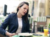 Stock Video Footage of Businesswoman gets stomach ache during lunch in cafe NTSC