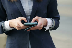 Businesswoman texting on smartphone by the city street NTSC - stock footage