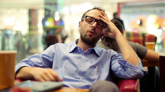 Sad young handsome man sitting in cafe HD Stock Footage
