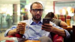 Handsome young man texting on smartphone in cafe HD Stock Footage