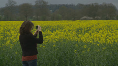 Speeding car passes photographer in Rapeseed Field Stock Footage