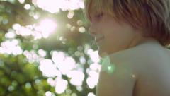 Profile Of Little Boy Smiling In A Tree (With Beautiful Lens Flare) Stock Footage