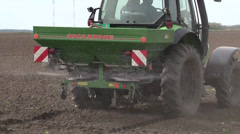 tractor spreading artificial fertilizer close up from back - stock footage