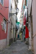 Cobblestone Alfama street with laundry hanging Stock Photos