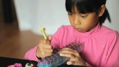 Girl Uses Hook On Her Bracelet Loom Stock Footage