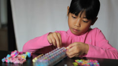 Cute Girl Making Colorful Bracelet On Loom Stock Footage