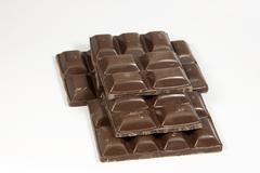 Stacked broken slab of dark chocolate squares Stock Photos