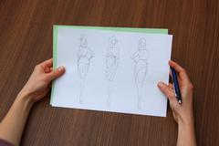 designer assessing fashion drawings - stock photo
