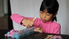Girl Works On Colorful Bracelet On With Her Loom Stock Footage