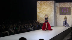 Blonde in dress by Olga Ibragimova goes on catwalk Stock Footage
