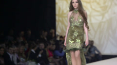 Model in glisten dress walks on podium at Volvo Fashion Week Stock Footage