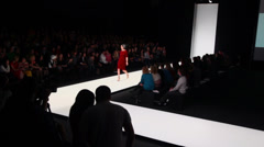 Model walks by podium during fashion show Stock Footage