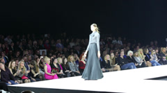 Audience look at model in long dress on catwalk in Gostiny Dvor Stock Footage