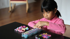 Eight Year Old Girl Makes Bracelet On Her Loom Stock Footage