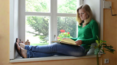 Serious face woman sit on sill watch window and read book Stock Footage