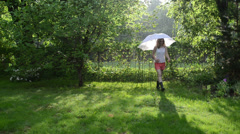 Rainy park and woman in shorts and gumboots walk with umbrella Stock Footage