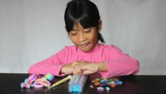 Asian Girl Enjoys Making A Bracelet On Her Loom Stock Footage