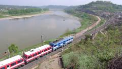 Locomotive of a train is moving rapidly along a river, with sound Stock Footage