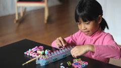 Little Girl Making Rainbow Bracelet On Her Loom Stock Footage